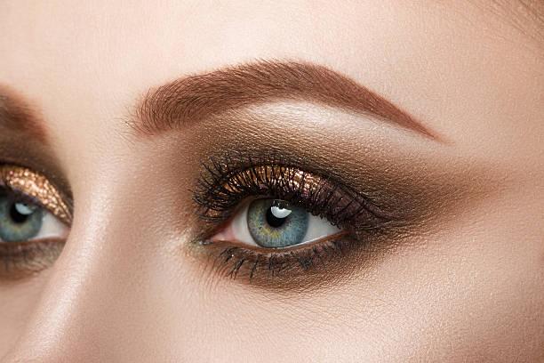 close-up auf weibliche blaues auge - goldenes augen make up stock-fotos und bilder