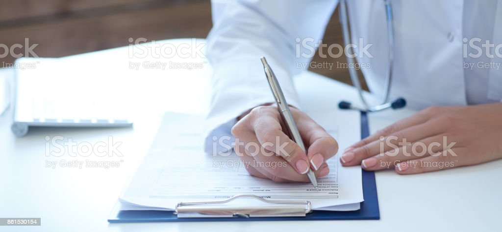 Close-up view of female doctor hands filling patient registration...