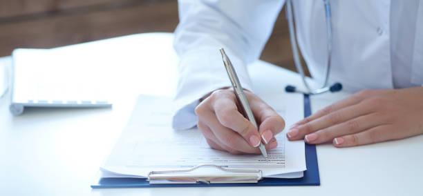 Nahaufnahme der Ärztin Hände Patientenanmeldung Formular ausfüllen. Gesundheitswesen und medizinische Konzept. – Foto