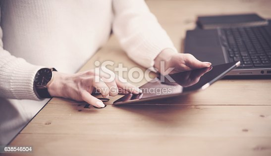 629421870 istock photo Closeup view of female hand touching tablet display on workplace 638546504