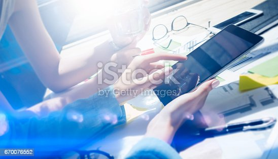 istock Closeup view of female hands holding modern digital tablet.Girl pointing the screen with your finger.Concept business people working with mobile gadgets.Visual effect,flares,blurred background. 670076552
