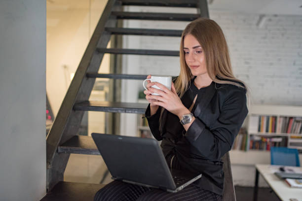 close-up view of female worker holding laptop writing email in office building - dtephoto stock photos and pictures