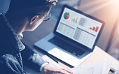 istock Closeup view of finance market analyst in eyeglasses working at sunny office on laptop while sitting at wooden table.Businessman analyze stock report on notebook screen.Blurred background,horizontal. 815169244