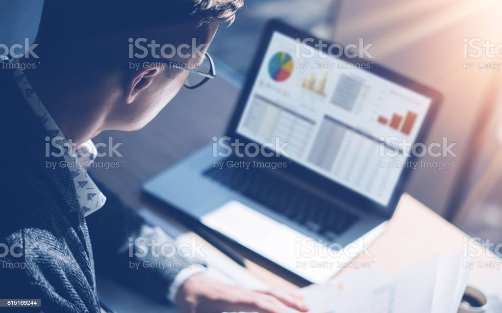 Closeup view of finance market analyst in eyeglasses working at sunny office on laptop while sitting at wooden table.Businessman analyze stock report on notebook screen.Blurred background,horizontal. stock photo