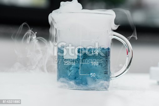 Close-up view of flask with blue reagent and steam in chemical lab