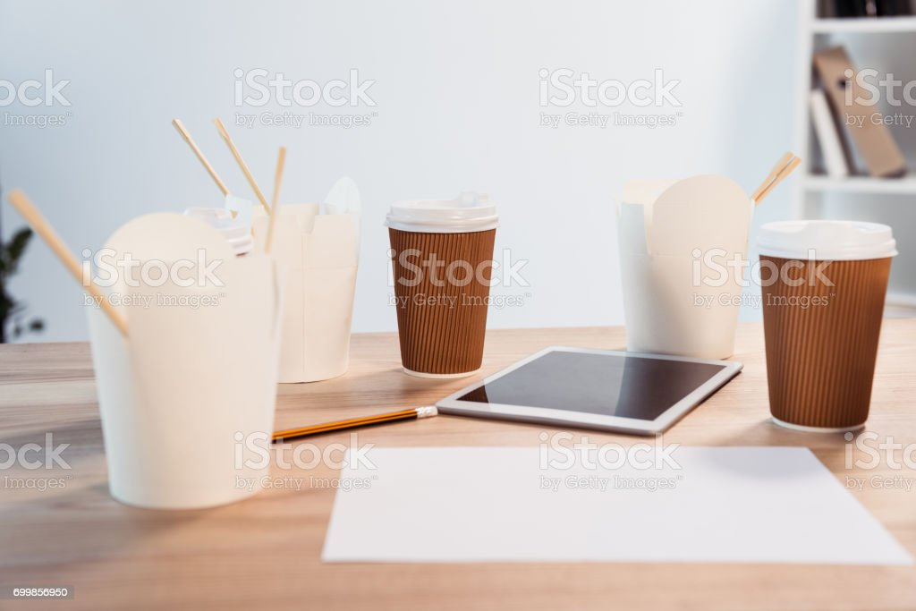Close-up view of food boxes with chopsticks, disposable coffee cups and digital tablet on office table stock photo