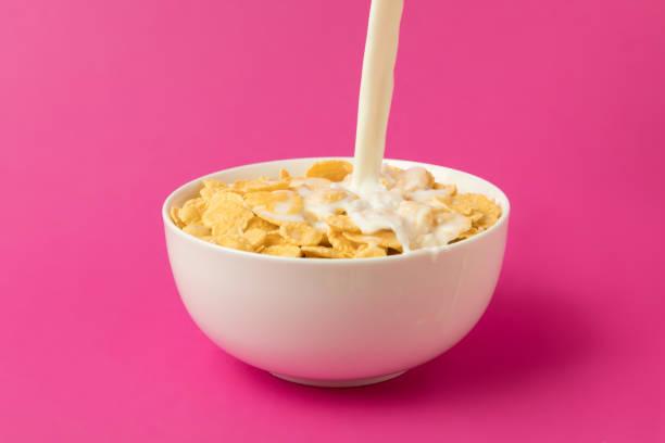 vista cercana de la leche, verter en recipiente con copos de maíz aislados en rosa - corn flakes fotografías e imágenes de stock