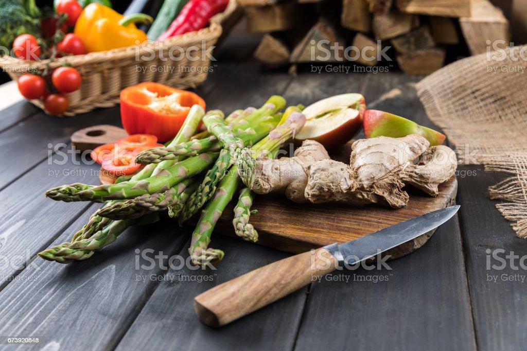 Vue rapprochée des légumes frais de saison et pommes coupées en deux sur le dessus de table en bois photo libre de droits
