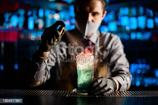 close-up view of beautiful glass with cold blue cocktail with ice that male bartender in gloves holds and sprinkles on it