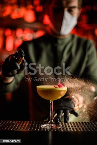 close-up view of glass with alcoholic cocktail decorated with flower on which man bartender carefully sprinkles