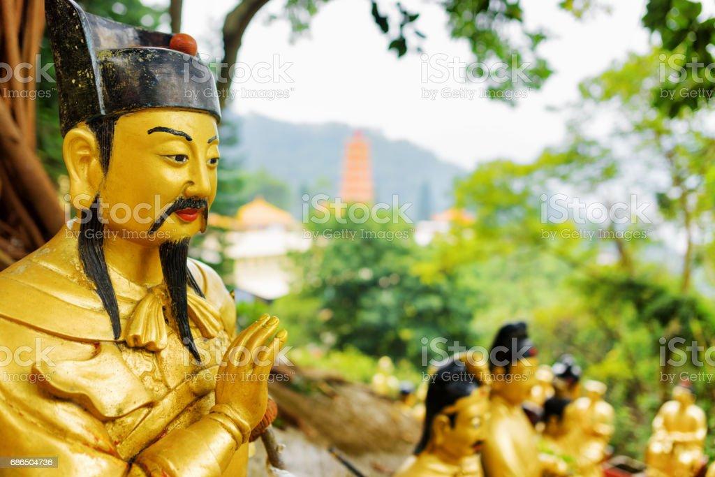 Närbild bild av gyllene Buddha staty på bakgrund av en röd pagoda och skog i Hong Kong royaltyfri bildbanksbilder