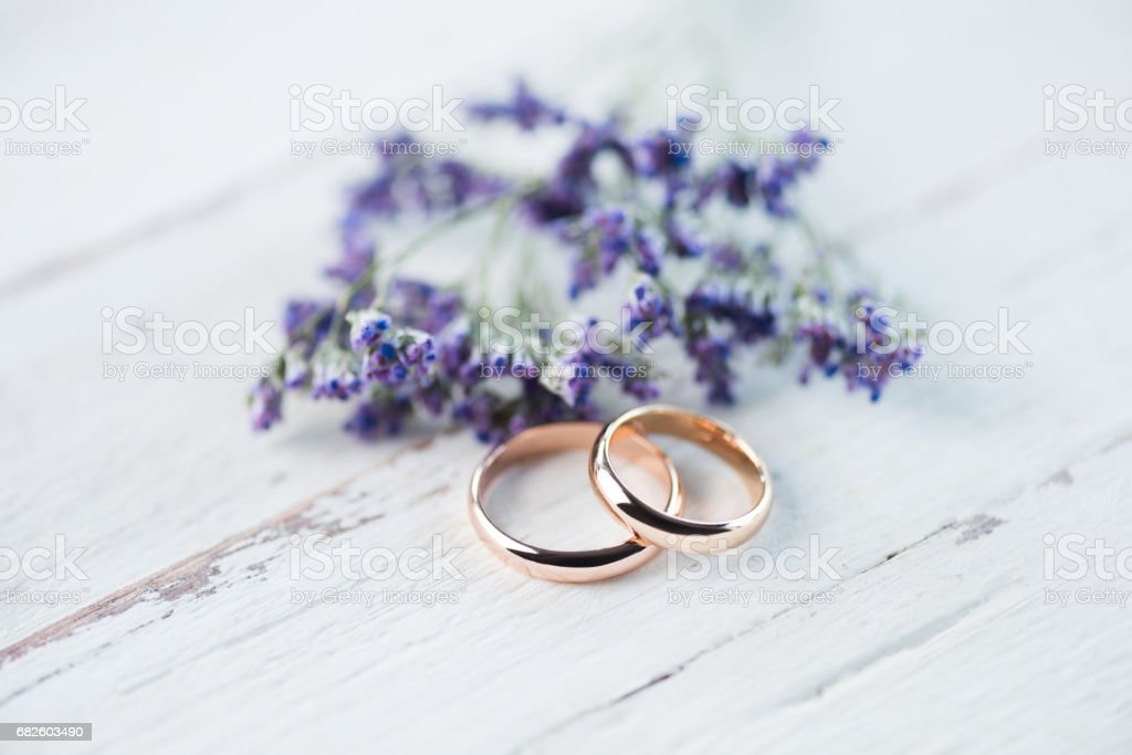 Close-up view of golden wedding rings and beautiful small blue flowers on wooden tabletop stock photo