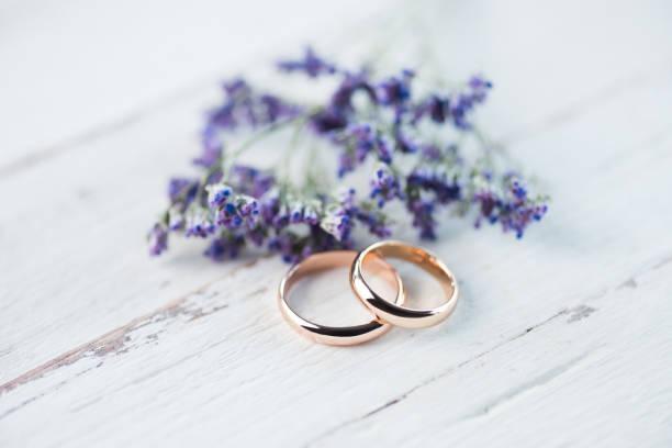 close-up view of golden wedding rings and beautiful small blue flowers on wooden tabletop - tischdeko goldene hochzeit stock-fotos und bilder