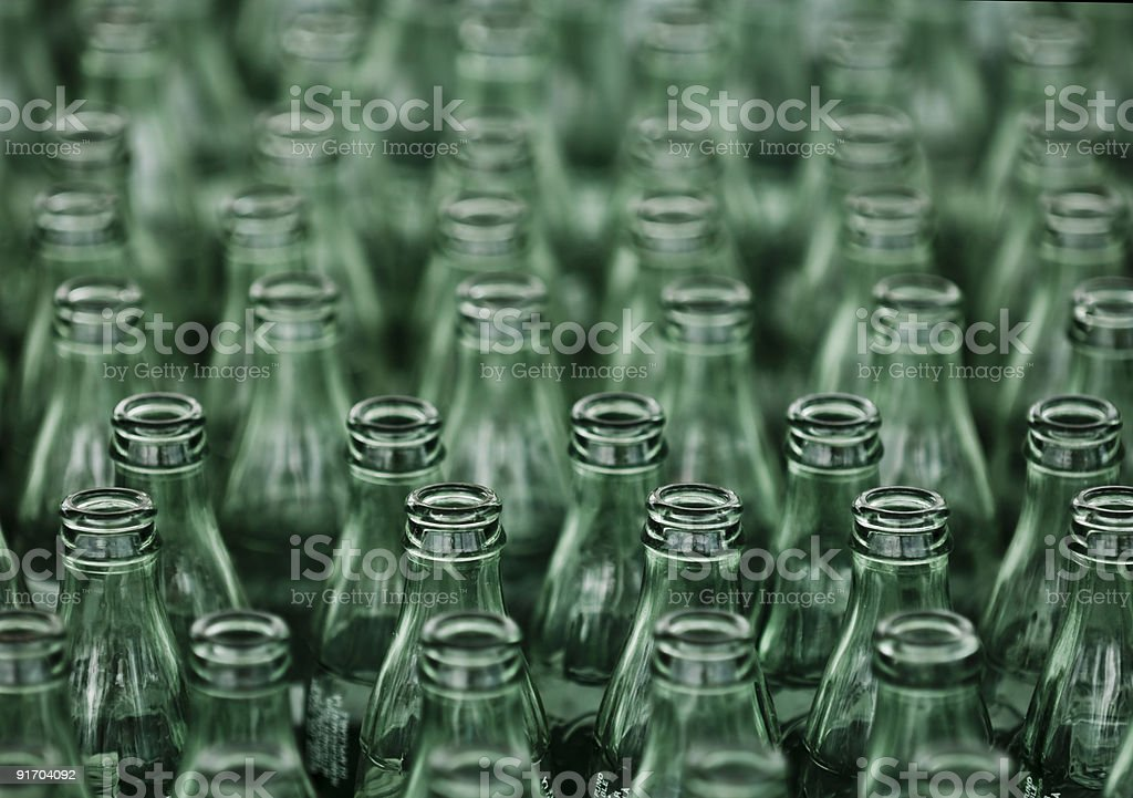 A closeup view of green glass bottles about to be recycled stock photo