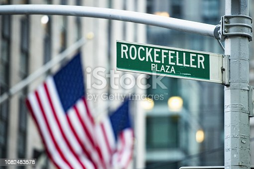 (selective focus) Close-up view of green street sign depicting 'Rockefeller Plaza' in Midtown Manhattan, New-York. Blurred American flags in the background.