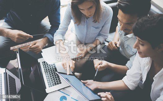 istock Closeup view of group young coworkers working on mobile laptop computer at office.Woman holding tablet and pointing on touch screen. Horizontal, blurred background. 931829824