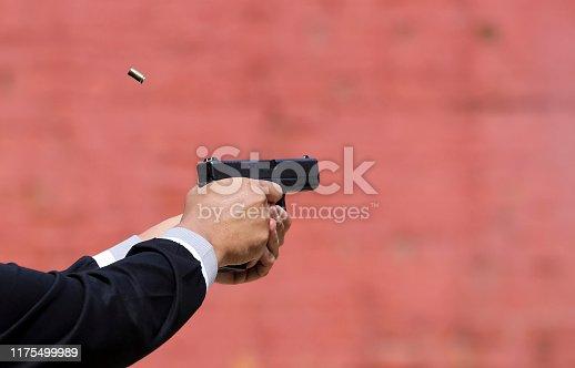 1048647890 istock photo Closeup view of hand holding a pistol / handgun taking aim for target 1175499989