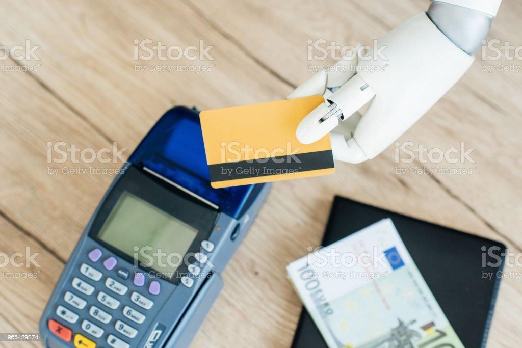 手持信用卡的機器人手特寫圖與木桌上的支付終端 - 免版稅人工造的圖庫照片