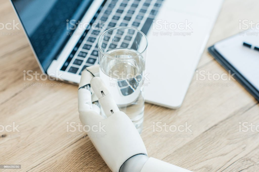 在木桌上手持玻璃水的機器人手特寫圖 - 免版稅人工造的圖庫照片