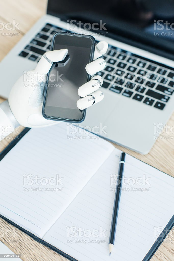 close-up view of hand of robot holding smartphone with blank screen at workplace zbiór zdjęć royalty-free