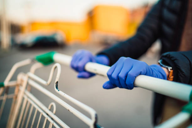 Close-up view of hands in rubber gloves pushing shopping carts. Close-up view of hands in rubber gloves pushing shopping carts in front of supermarket. protective glove stock pictures, royalty-free photos & images