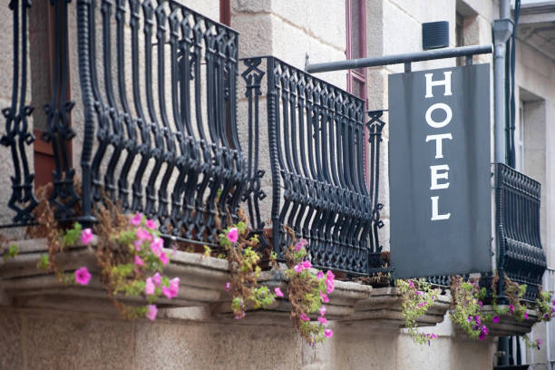 Close-up view of hotel sign on building facade with cast iron balconies. stock photo