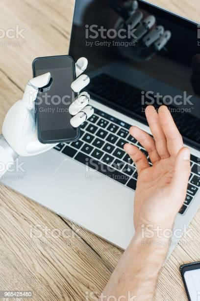 Foto de Closeup Vista Das Mãos De Humanos E Robôs Usando Smartphone E Laptop Na Mesa De Madeira e mais fotos de stock de Braço robótico