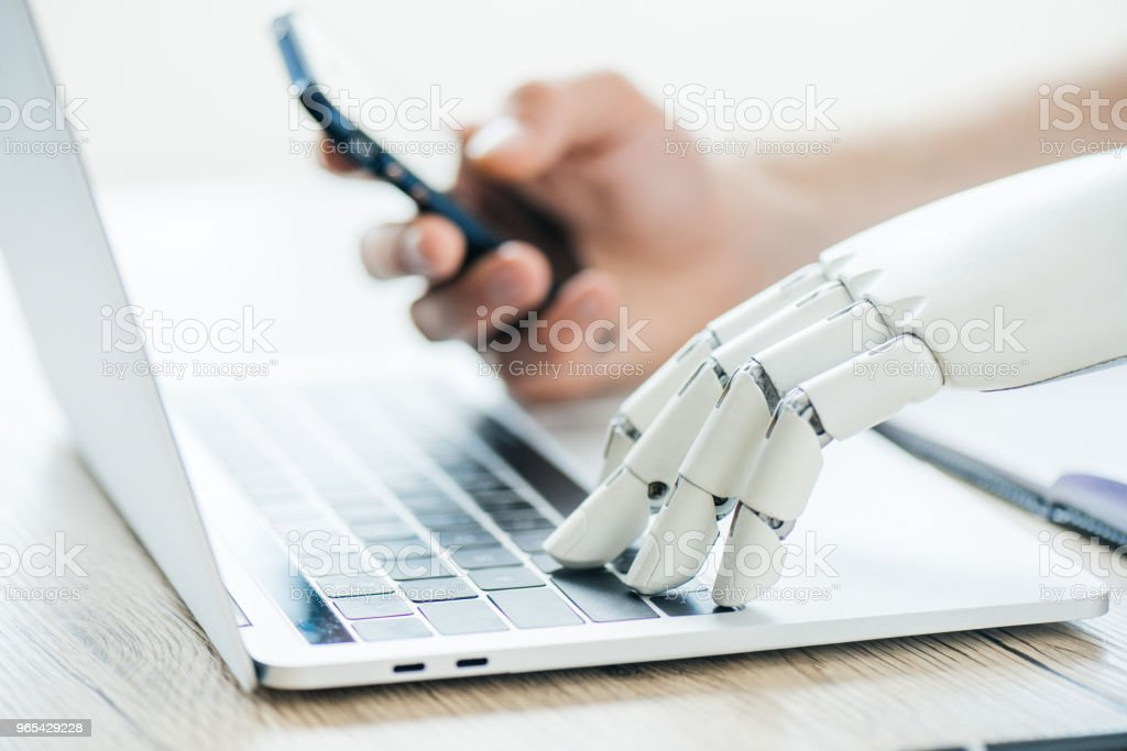 close-up view of human and robot hands using smartphone and laptop at wooden table zbiór zdjęć royalty-free