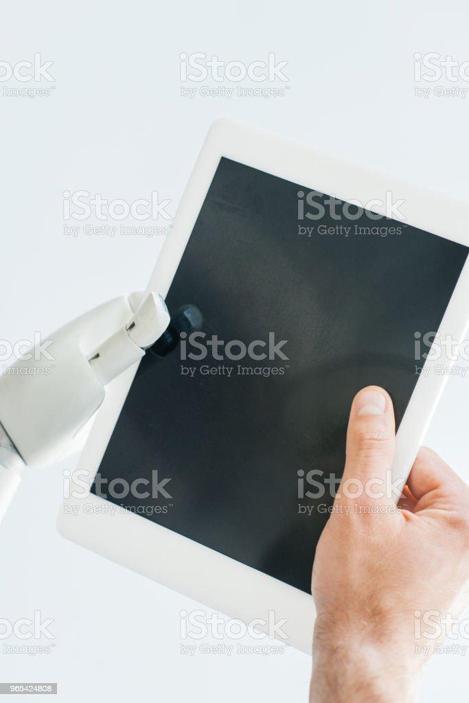 vue rapprochée de la main de l'homme et le bras tenant la tablette numérique avec écran blanc isolé sur blanc - Photo de Artificiel libre de droits