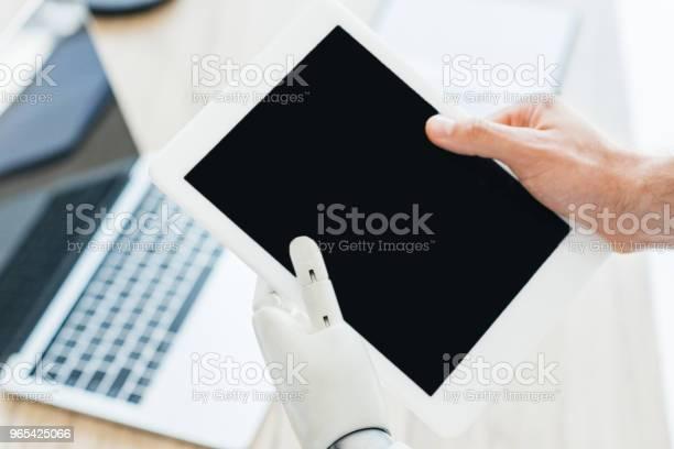 Foto de Closeup Vista Da Mão Humana E Braço Robótico Segurando O Tablet Digital Com Tela Em Branco e mais fotos de stock de Braço robótico