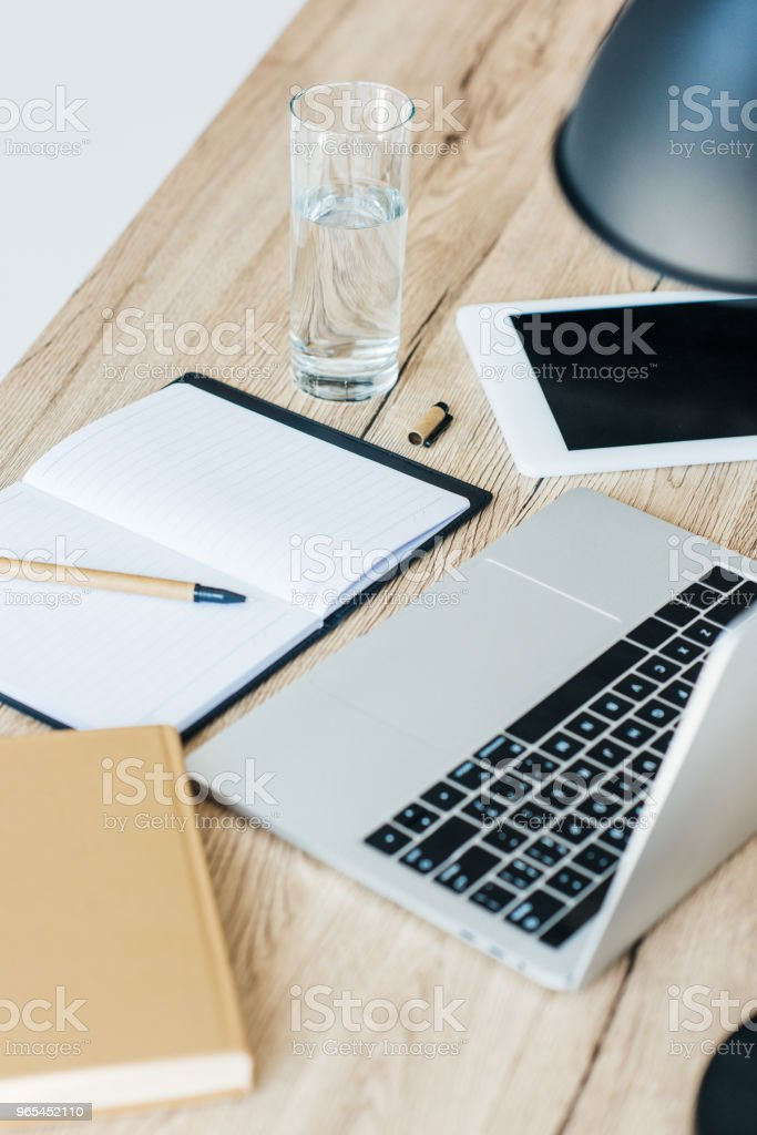 close-up view of laptop, digital tablet, glass of water and notebook at workplace royalty-free stock photo