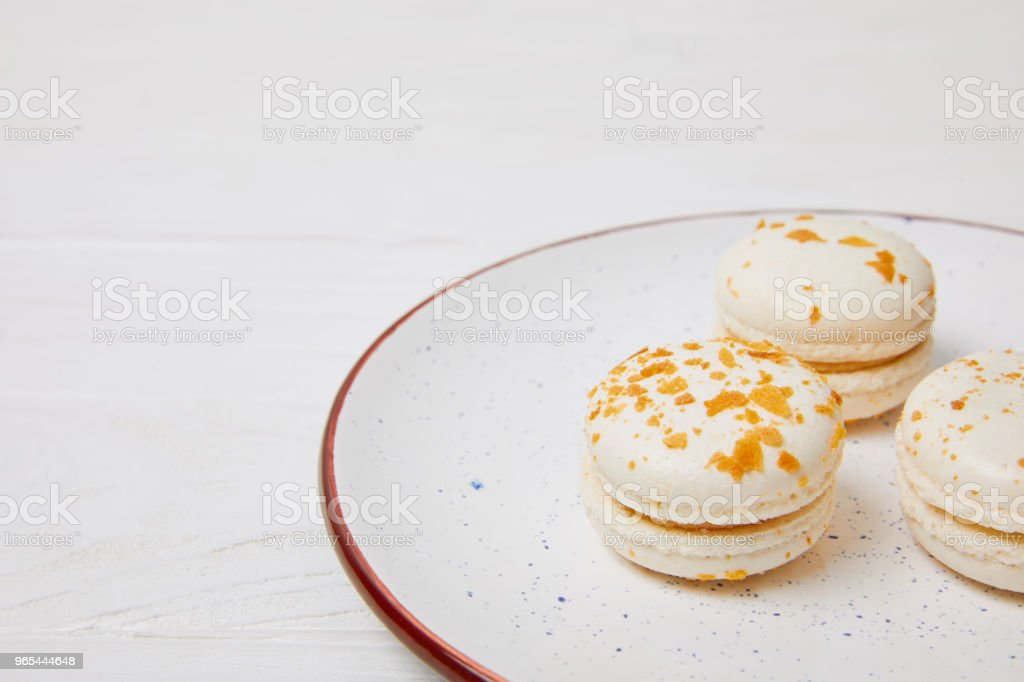 closeup view of macarons in plate on white wooden table royalty-free stock photo
