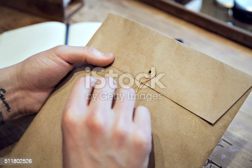 879813798istockphoto Close-up view of male hands holding envelope wooden desk 511802526