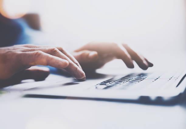 Detailansicht der männlichen Hände auf Laptoptastatur tippen. Der Hintergrund jedoch unscharf, horizontale. Selektiven Fokus auf Händen. – Foto