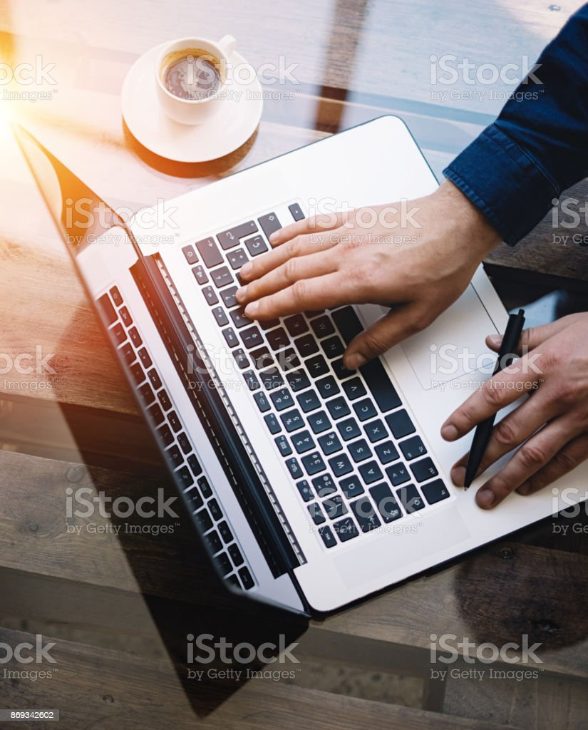Closeup view of Man typing laptop keyboard while sitting at the wooden table.Reflections on glass surface.Top view.Horizontal.Visual effects. stock photo