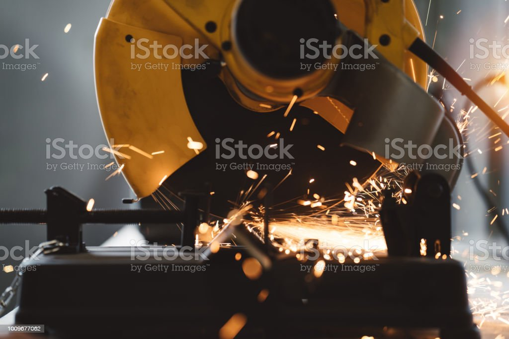 Close-up view of metalworking on angular grinding machine in workshop. Sparks fly apart. Work in process. Flare effect stock photo