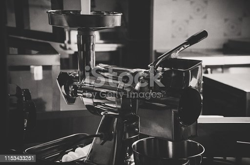 Close-up view of modern meat grinder. Black and white.