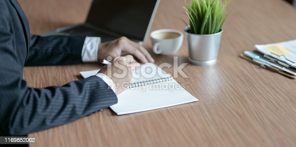 1068752548istockphoto Close-up view of motivated businessman writing his idea 1169852002