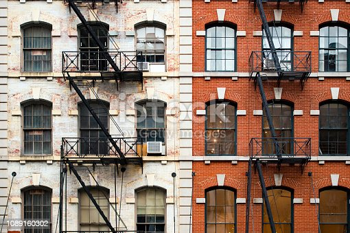 Close-up view of New York City style apartment buildings with emergency stairs along Mott Street in Chinatown neighborhood of Manhattan, New York, United States..