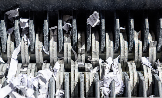 istock closeup view of office paper shredder teeth 1169822748