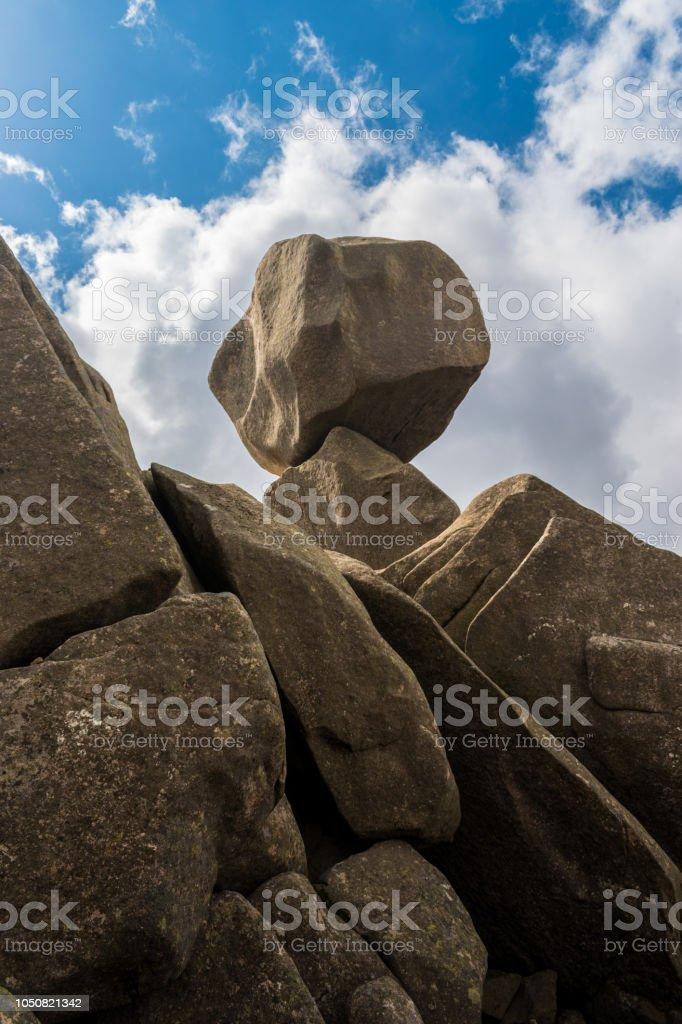 Closeup vista Omu di Cagna (Uomo di Cagna) na ilha de Córsega. A pedra de granito é equilibrada no topo de um pico na montanha de Cagna, rodeado por nuvens e céu azul. - foto de acervo