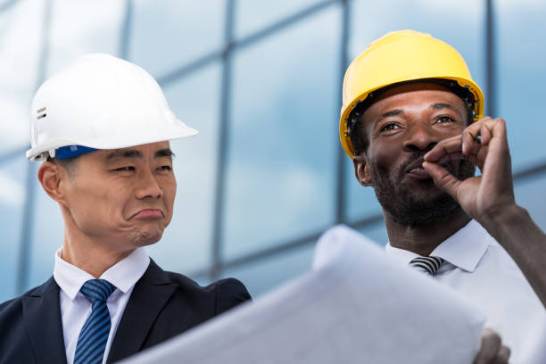 Close-up view of professional architects in hardhats working with blueprint stock photo