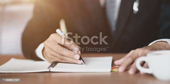 1068752548istockphoto Close-up view of professional businessman writing his idea 1169852031