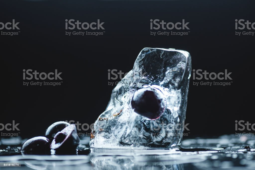 close-up view of ripe sweet cherries with melting ice cube on black stock photo