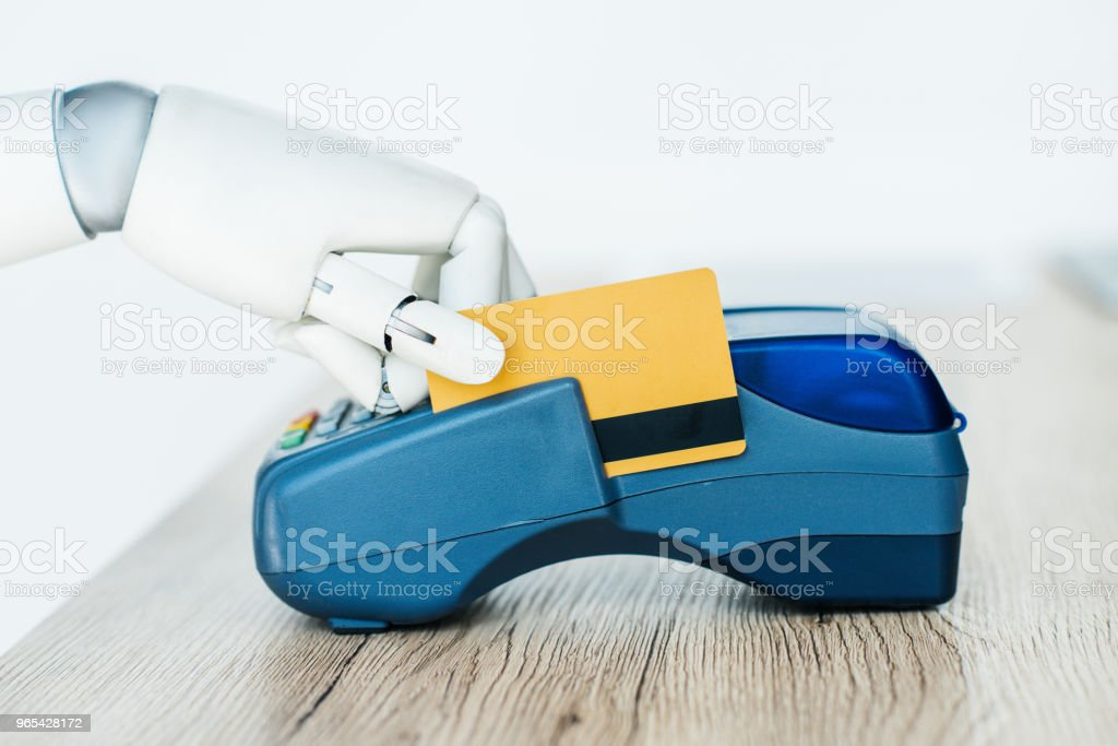 close-up view of robot holding credit card and using payment terminal royalty-free stock photo