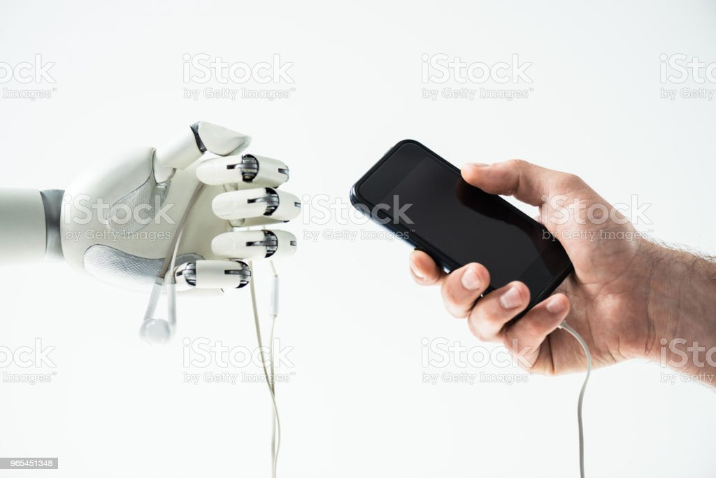close-up view of robot holding earphones and human hand holding smartphone isolated on white zbiór zdjęć royalty-free