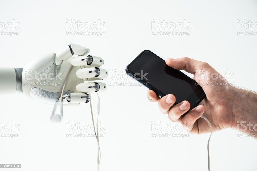 로봇 이어폰 및 인간의 손을 잡고 스마트폰 흰색 절연의 근접 보기 - 로열티 프리 STEM-주제 스톡 사진