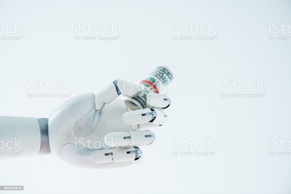 close-up view of robot holding rolled dollar banknotes isolated on white zbiór zdjęć royalty-free