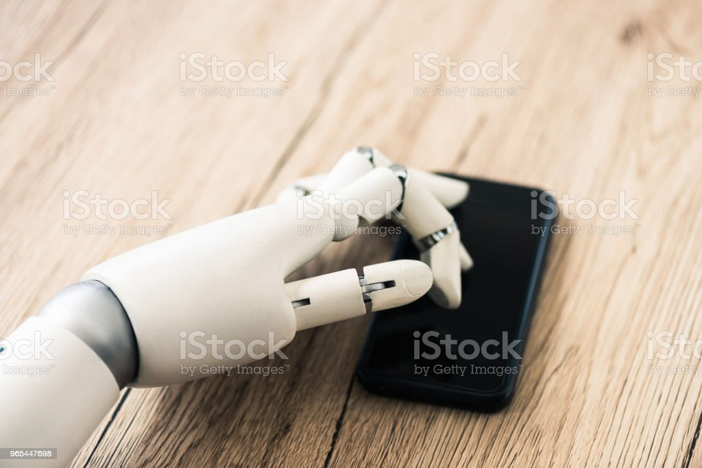 close-up view of robot using smartphone on wooden table zbiór zdjęć royalty-free