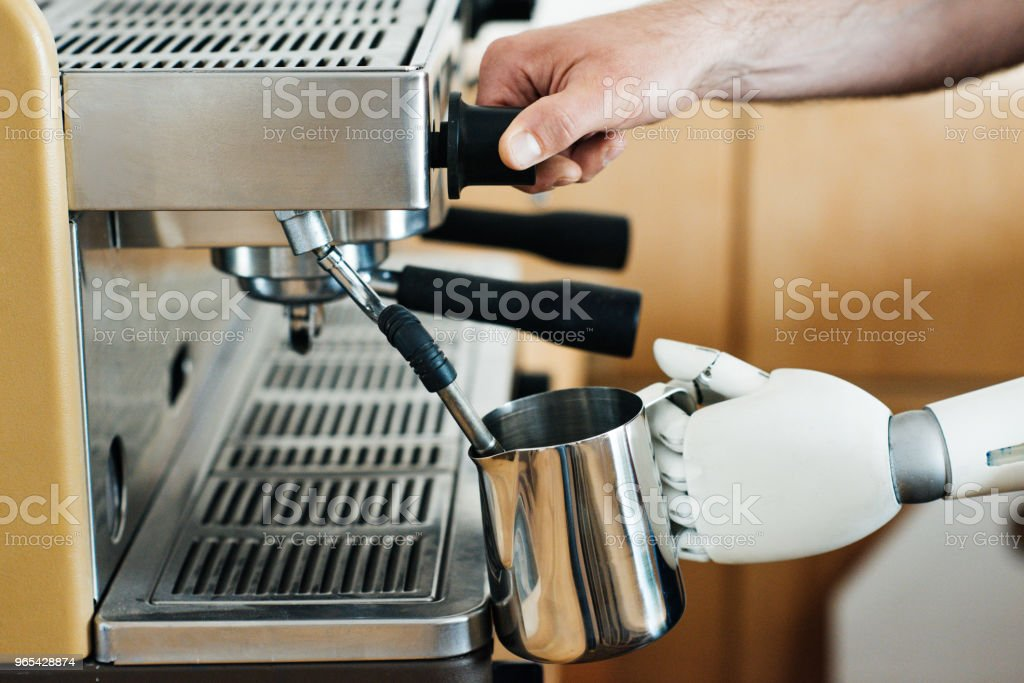 close-up view of robotic arm and human hand preparing coffee in coffee machine royalty-free stock photo